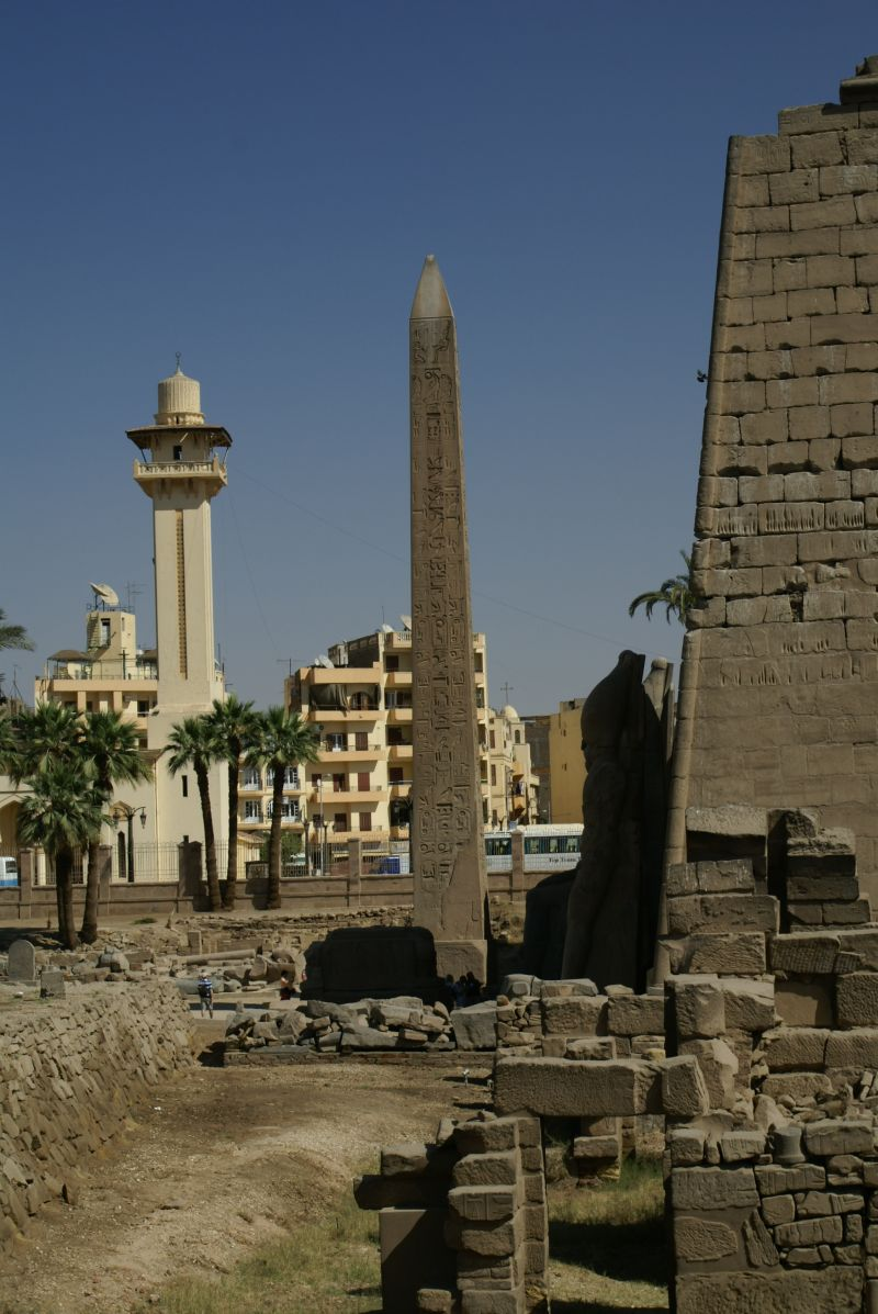 An obelisk within luxor temple with the luxor mosque in the background
